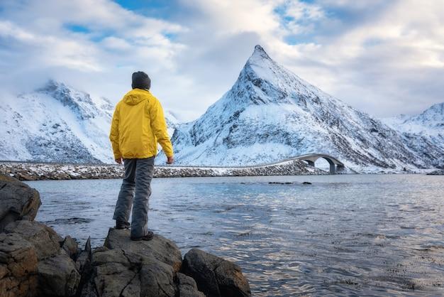 Sportlicher mann in der gelben jacke, die auf dem stein auf seeküste gegen schneebedeckte berge und bewölkten himmel am sonnenuntergang im winter steht