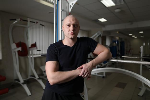 Sportlicher mann in der schwarzen sportkleidung. tragendes t-shirt des jungen kerls und entspannung in der turnhalle. workout und pause-konzept. schöner sportler bodybuilder