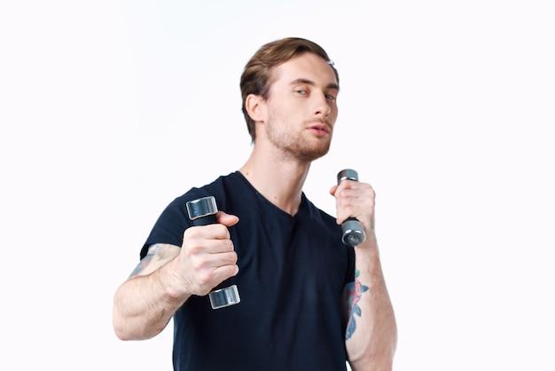 Sportlicher mann in einem schwarzen t-shirt mit hanteln in den händen auf einem weißen