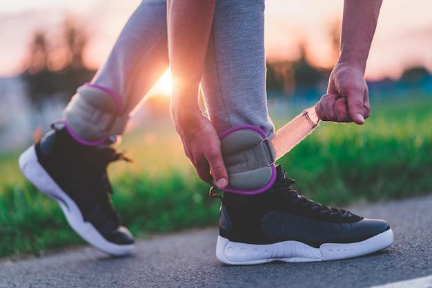 Sportlicher mann legt sportgewichte für das gehen während des trainings im freien an. gesunder und sportlicher lebensstil.