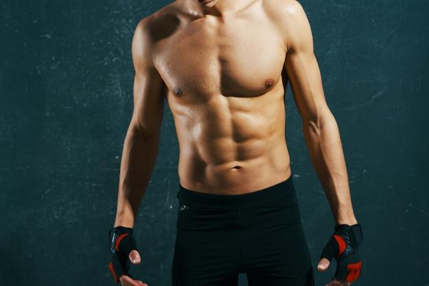 Sportlicher mann mit aufgepumptem körpertraining trainiert dunklen hintergrund