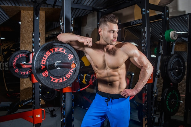 Sportlicher mann mit den großen muskeln an der turnhalle