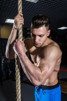 Sportlicher mann mit den großen muskeln ausbildend in der turnhalle, in der eignung und in der aufgepumpten bauchpresse
