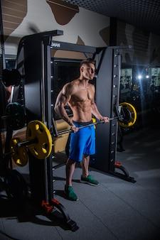 Sportlicher mann mit den großen muskeln und den breiten hinteren zügen in der turnhalle