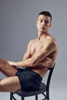 Sportlicher mann mit einem aufgepumpten körper, der auf einem stuhl sitzt, der aufwirft. hochwertiges foto