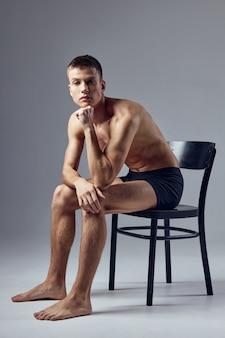 Sportlicher mann mit einem aufgepumpten körper in schwarzen shorts sitzt auf einem stuhl