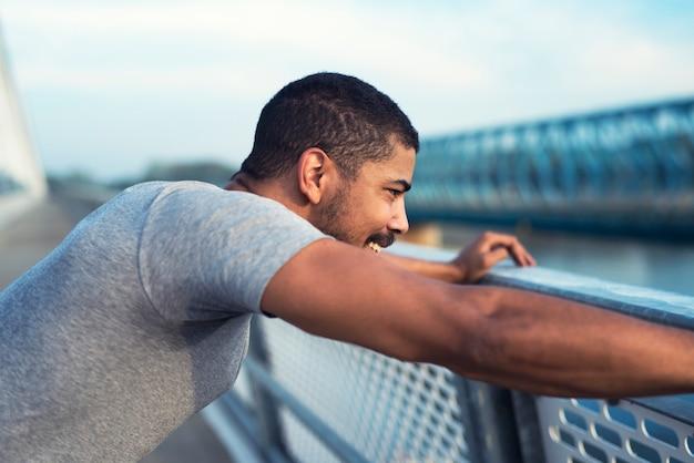 Sportlicher mann mit einem lächeln im gesicht, das konzentriert und bereit für das training wird