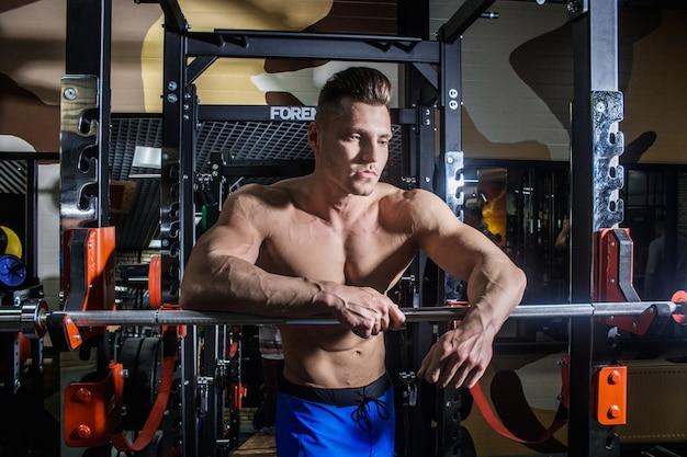 Sportlicher mann mit großen muskeln und breitem rücken trainiert im fitnessstudio, fitness und aufgepumpter bauchpresse. sexy mann im fitnessstudio mit hanteln.
