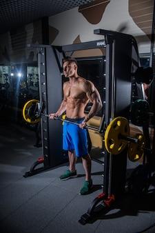 Sportlicher mann mit großen muskeln und breitem rücken trainiert im fitnessstudio, fitness und aufgepumpter bauchpresse. sexy mann in der turnhalle mit hanteln. russland, swerdlowsk, 2. juni 2018