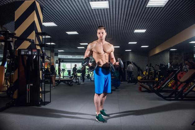 Sportlicher mann mit großen muskeln und einem breiten rücken trainiert in der turnhalle, eignung