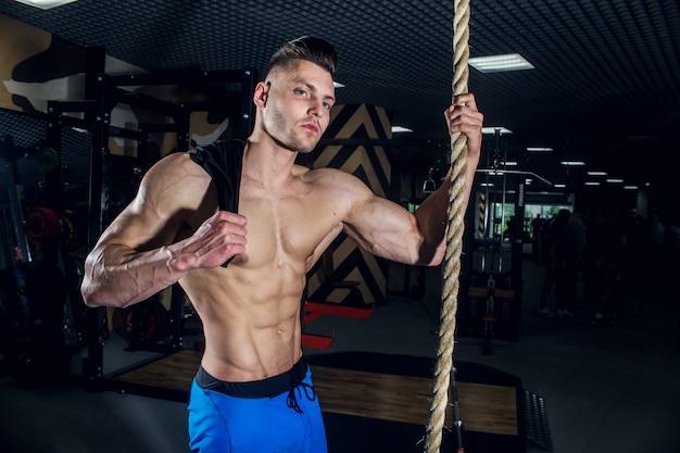 Sportlicher mann mit großen muskeln und einem breiten rücken trainiert