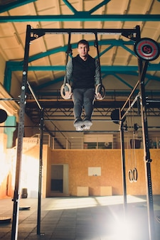 Sportlicher mann mit muskelaufbau, der intensives training im fitnessstudio auf turnringen durchführt.