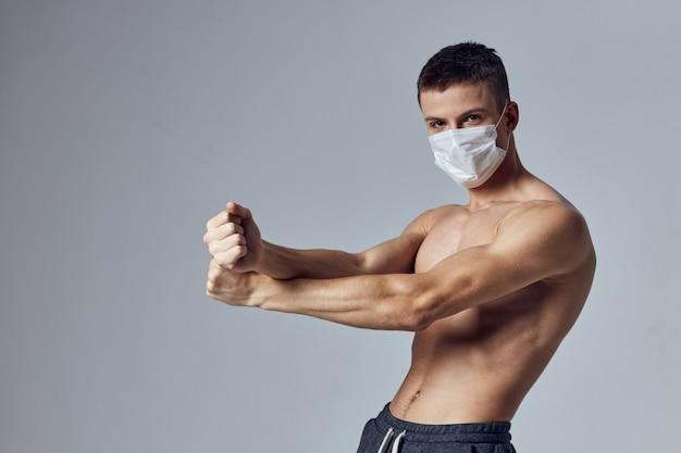 Sportlicher mann mit muskulöser körpermedizinmaske, die fitnessstudio aufwirft.