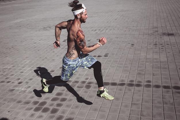 Sportlicher mann mit nacktem oberkörper mit tätowierungen und stirnband auf dem kopf in schwarzen leggings und blauen shorts läuft an einem warmen sonnigen tag auf pflastersteinen.