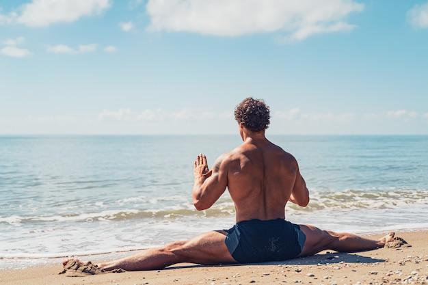 Sportlicher mann mit schönen muskeln sitzt auf einer schnur im sommertraining an der küste