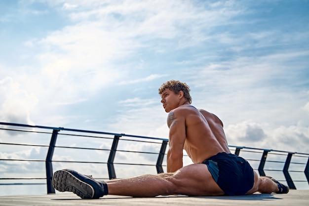 Sportlicher mann mit schönen muskeln sitzt auf einer schnur im sommertraining auf einem pier am meer