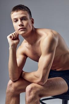 Sportlicher mann pumpte muskulösen körper auf, der auf stuhl aufwirft aufwirft.