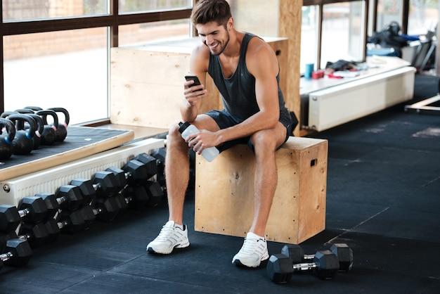 Sportlicher mann sitzt auf der kiste im fitnessstudio und schaut auf das handy