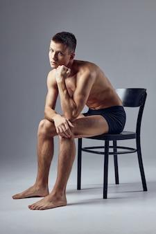 Sportlicher mann sitzt auf stuhl nachdenklich aussehen fitness-lebensstil. hochwertiges foto