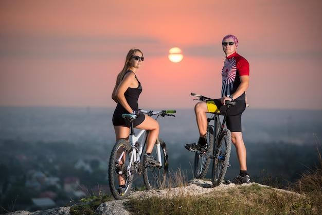 Sportlicher mann und frau auf mountainbikes, die auf den klippenfelsen stehen