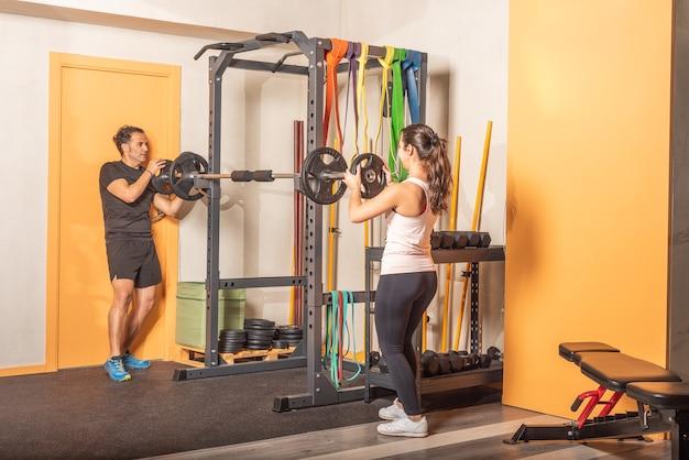 Sportlicher mann und frau, die hantelscheibe auf die stange im fitnessstudio legen. konzept der ausrüstung im fitnessstudio.