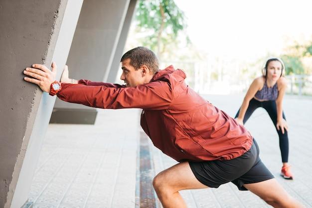 Sportlicher mann und frau, die in städtische umwelt ausdehnen