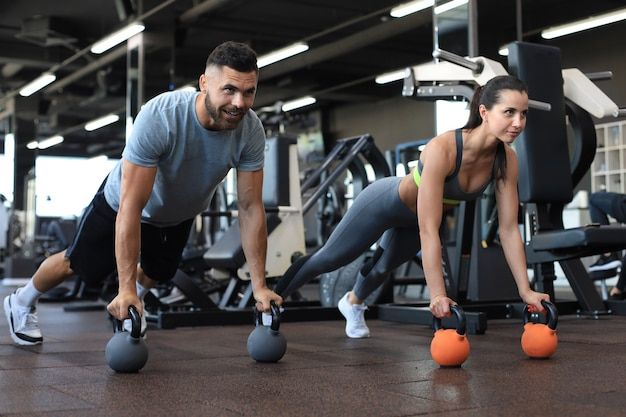 Sportlicher mann und frau, die liegestütze in einem fitnessstudio machen.
