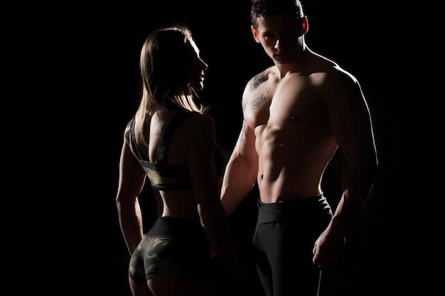 Sportlicher mann und frau. silhouetten auf schwarzem hintergrund.