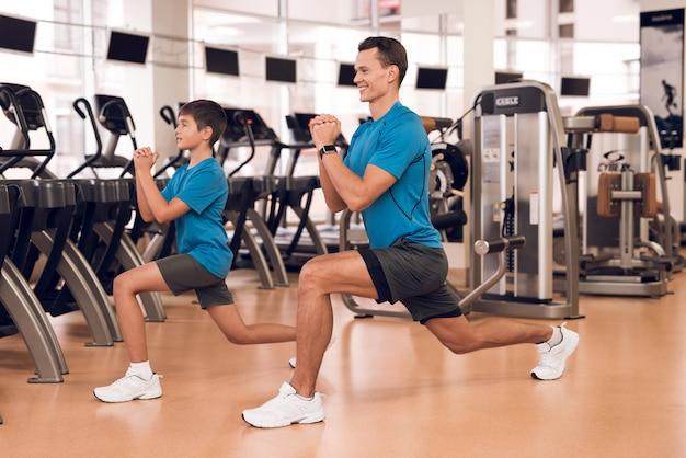 Sportlicher mann und junge nahe tretmühlen in der modernen turnhalle