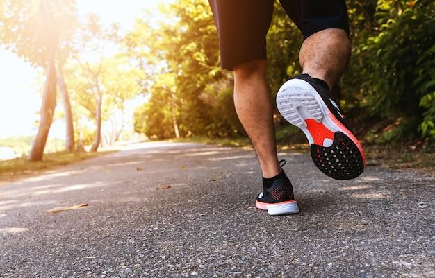 Sportlicher mannläufer, der auf straßen im park mit weichzeichner und über licht im hintergrund läuft
