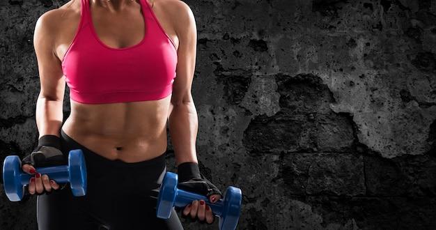 Sportlicher muskulöser frauentrainingsbizeps mit hanteln auf grunge-hintergrund