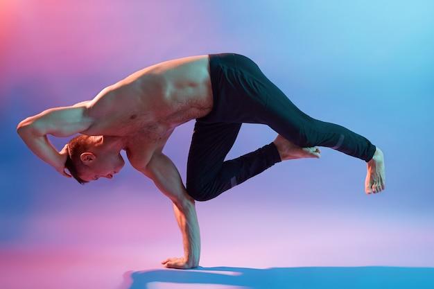 Sportlicher muskulöser junger mann, der yoga praktiziert, das übungen für körperausgleich macht