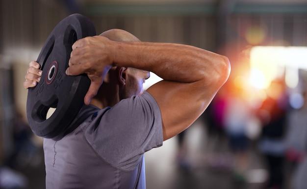 Sportlicher muskulöser mann, der muskeln im fitnessstudio trainiert