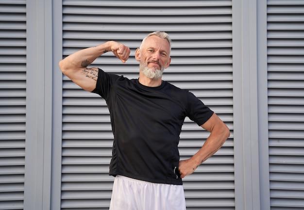 Sportlicher reifer mann, der in die kamera schaut und seinen muskulösen arm und bizeps zeigt, während er im freien steht
