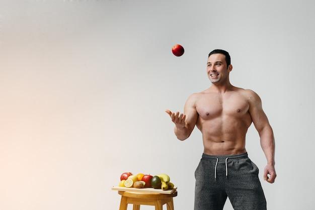 Sportlicher sexy kerl, der auf einem weiß mit hellen früchten aufwirft. diät. gesunde ernährung.