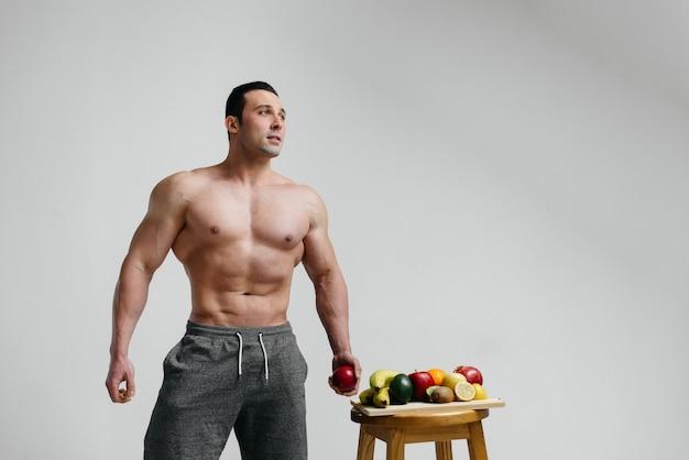 Sportlicher sexy kerl, der auf einem weißen hintergrund mit hellen früchten aufwirft. diät. gesunde ernährung.