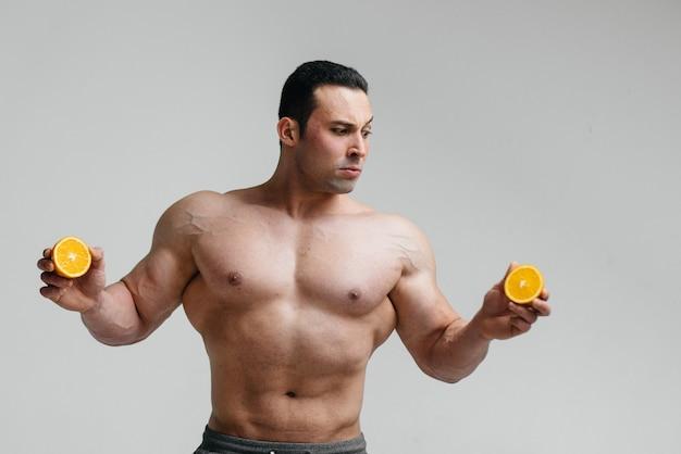 Sportlicher sexy kerl, der auf einem weißen hintergrund mit hellen früchten aufwirft. diät. gesunde ernährung