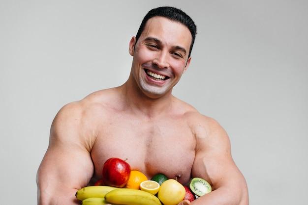 Sportlicher sexy kerl, der auf einem weißen raum mit hellen früchten aufwirft. diät. gesunde ernährung.