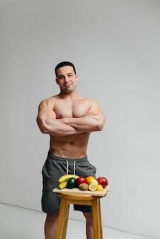 Sportlicher sexy kerl, der auf weiß mit hellen früchten aufwirft. diät. gesunde ernährung.
