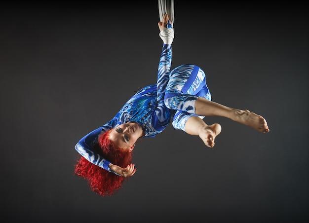 Sportlicher sexy luftzirkuskünstler mit rotschopf im blauen kostüm, der in der luft mit gleichgewicht tanzt. Premium Fotos