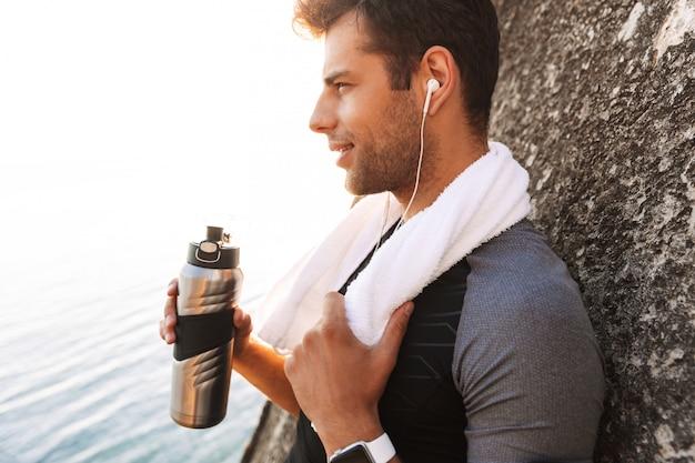 Sportlicher typ im trainingsanzug, der musik über drahtlose kopfhörer hört und wasser aus metallbecher trinkt