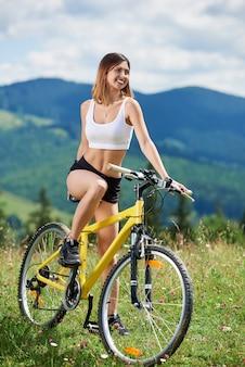 Sportlicher weiblicher biker, der auf gelbem mountainbike auf einem gras radelt und sommertag in den bergen genießt