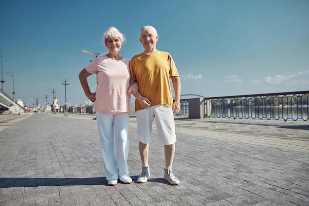 Sportliches älteres ehepaar in freizeitkleidung, das in die kamera lächelt