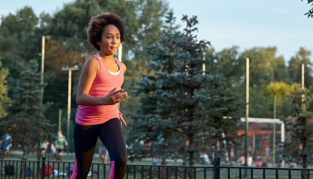Sportliches afroamerikanisches mädchen, das auf der straße läuft