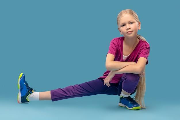 Sportliches aufwärmen. selbstbewusstes süßes mädchen in sportkleidung und turnschuhen hockte mit ihrem zur seite ausgestreckten bein auf blauem hintergrund
