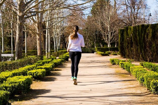 Sportliches blondes mädchen, das in einem park läuft. sportkonzept