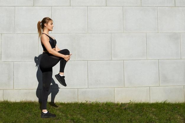 Sportliches blondes mädchen mit pferdeschwanz und athletischem körpertraining im park am morgen, dehnen der beinmuskeln nach cardio-training, aufwerfen gegen grauen backsteinmauerhintergrund mit kopienraum für ihren text