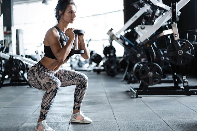 Sportliches fitnessmodell der jungen frau, das kniebeugenübung ausführt
