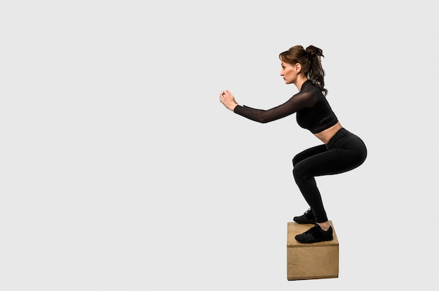 Sportliches frauentraining, das muskeln von händen und beinen aufpumpt. frau in schwarzer sportbekleidung. kraft und motivation. seitenansicht