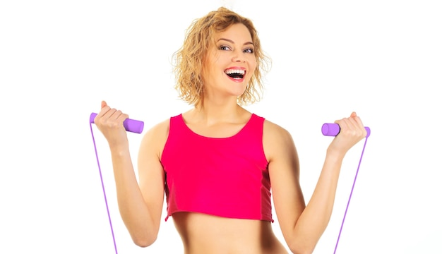 Sportliches frauentraining mit springseil. lächelnder fitnesstrainer mit springseil. fitness, aktivität, sport-lifestyle.